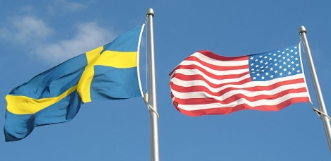 A Swedish flag and an American flag fly side by side.