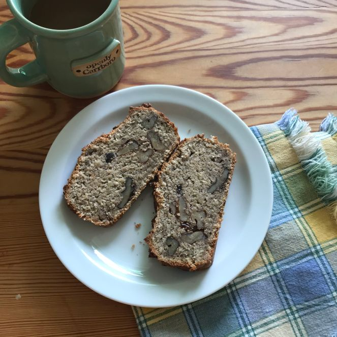 two slices of banana bread on a plate on a table next to a green mug.