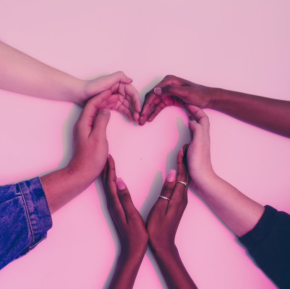 Several hands of various skin tones creating the shape of a heart
